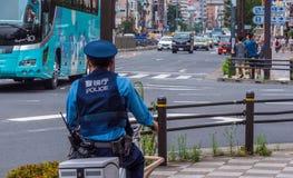 Policier japonais sur une bicyclette dans les rues de Tokyo - TOKYO, JAPON - 12 juin 2018 photo stock