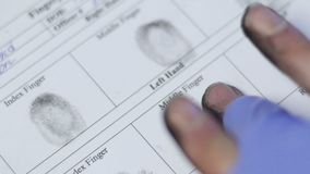 Policier prenant des empreintes digitales de principal suspect, marque biométrique d'identificateur banque de vidéos
