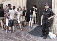 Policier se tenant à côté d'un défilé gai de rue Photographie stock