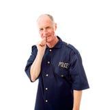 Policier souriant avec le doigt dans la bouche Photographie stock