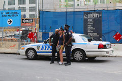 Policiers de NYPD prenant la photo avec le World Trade Center proche de touristes à Manhattan Photos libres de droits