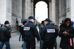 Policiers parmi les passants près de la voûte triomphale photos stock