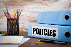 Policies, Office Binder on Wooden Desk. On the table colored pen. Cils, pen, notebook paper Royalty Free Stock Photo