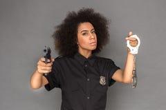 policja Oliwkowa kobiety pozycja odizolowywająca na popielatej wskazuje kamerze z armatnim mieniem zakłada kajdanki chłodno obraz stock