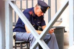 Policjant na jego telefonu komórkowego obsiadaniu Obrazy Royalty Free