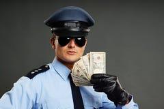 Policjant pokazuje pieniądze Obraz Royalty Free