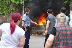 Policjant z pistoletem i ludźmi ogląda samochodowego palenie w Bucharest Fotografia Royalty Free