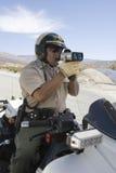 Policjanta monitorowanie prędkość Chociaż radaru pistolet Fotografia Stock