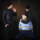 Policman and two thiefs. Police officer and two thiefs, they have captured him and tied him down Royalty Free Stock Image