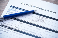 Policy change request form with blue pen , shallow depth of focu. S field on wooden table Stock Image