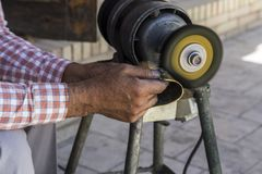 Polierarbeitskonzept Mann, der goldene Glocke auf Maschine poliert stockbild