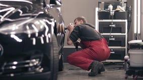 Polierauto mit polnischem mashine Arbeitskraft im roten Anzug, der ein schwarzes teures Auto säubert