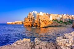 Polignano конематка, Апулия, Италия: Заход солнца на заливе Cala Paura с Bastione di Santo Stefano и ламом Monachile приставает к стоковые изображения