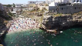 Polignano A Mare, Italy - August 4, 2017: aerial view of Polignano a mare beach and cliffs, Apulia, southern Italy.  stock footage