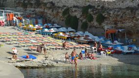 Polignano A Mare, Italy - August 4, 2017: crowded small beach with umbrellas and chairs, Apulia, Italy.  stock video