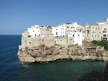 Polignano a Mare, Puglia, Italy. Scenery of Polignano a Mare, seaside gem in Puglia, with young people swimming in deep blu waters od Adriatic sea Royalty Free Stock Photo
