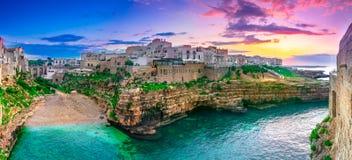 Polignano a Mare, Puglia, Italy: Sunset at Cala Paura gulf with Bastione di Santo Stefano and Lama Monachile beach. In background, Apulia, Italy, province of royalty free stock image