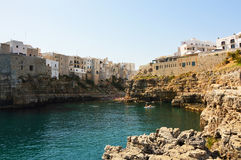 Polignano a mare village on cliff rocks and Mediterranean sea. Overhanging buildings in Apulia town on sea. Italian seascape. Stock Photos