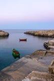Polignano une jument (BA) : côte des roches à coucher du soleil violet/bleu Un certain gozzo (bateaux de poissons) à l'ancre Photo libre de droits
