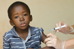 Polio Vaccination for African children from white volunteers in Africa. A nice shot of a little black African ethnicity boy getting a medical injection as a Stock Image