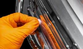 应用保护带的汽车波兰蜡工作者手在擦亮前 抛光的和擦亮的汽车 汽车详述 人举行a polis 免版税图库摄影