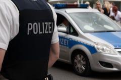 Polis framme av en folkmassa Arkivfoton