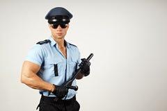 Polis med batongen Royaltyfria Bilder