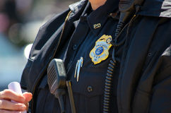 Polis med emblemet och likformign Royaltyfri Foto