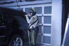 Polis med ficklampan som utforskar bilen i garage Arkivfoto