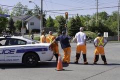 Polis- och säkerhetsbesättningen i mitt av vägen som håller ögonen på den kommande staden, ståtar arkivfoto