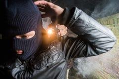 Polis som siktar pistolen in mot slagen sönder maskerad gangster på natten Arkivfoton