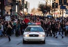 Polisbil framme av personerna som protesterar som kontrollerar trafiken Royaltyfria Foton