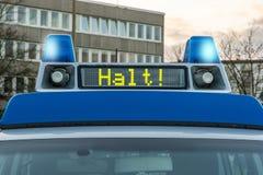 Polisbil med det tyska ordet för stopp! i skärmpanelen som ska kopplas på blått roterande ljus fotografering för bildbyråer