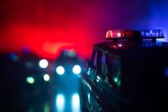 Polisbil som jagar en bil på natten med dimmabakgrund Bil för den 911 polisen för nöd- svar som rusar till platsen av brottet Sel royaltyfri foto
