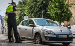 Polisen kontrollerar och skriver en trafikbiljett arkivfoton
