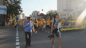 Polisen som eskorterar den aktiva folkmassan av svensk, fläktar att skynda sig till fotbollkonkurrens lager videofilmer