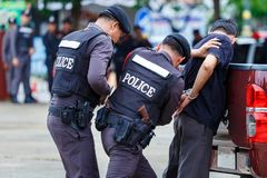 Polisen stålsätter handbojor, den arresterade polisen Royaltyfri Foto