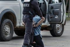 Polisen stålsätter handbojor, den arresterade polisen, den yrkesmässiga polisen måste vara mycket stark, tjänstemannen Arresting Arkivbild