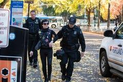 Poliser eskorterar ut den Antifa personen som protesterar royaltyfri bild