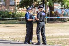 Poliser som framme talar av brottsplatsbandet royaltyfria bilder