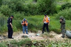 Poliser tar ut fisken från en fiskare för att tjuvjaga på den Oka floden royaltyfri fotografi