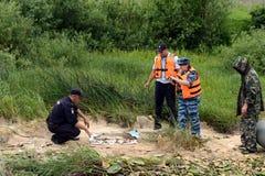 Poliser tar ut fisken från en fiskare för att tjuvjaga på den Oka floden arkivbilder