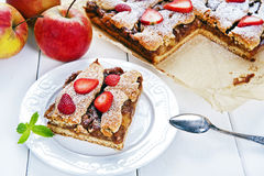 Polish apple pie with fresh strawberries on white table Stock Image