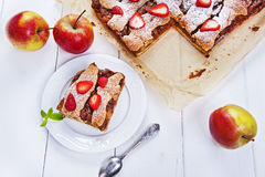 Polish apple pie with fresh strawberries on white table Royalty Free Stock Photos