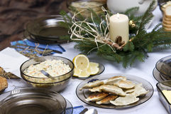 Polish Christmas table. A table set with some typically Polish dishes. All vegetarian foods. A decorative seasonal composition with a candle. Plate of pierogi in Royalty Free Stock Image