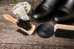 Polish cream, black boot,brush, and dirty cloth. Polish cream, black boot,brush and dirty cloth on wooden background royalty free stock images