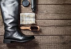Polish cream, black boot,brush, and dirty cloth. Polish cream, black boot,brush and dirty cloth on wooden background stock photo