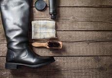 Polish cream, black boot,brush, and dirty cloth. Polish cream, black boot,brush and dirty cloth on wooden background Stock Photo