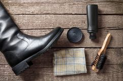 Polish cream,brush,dirty cloth and black boot. On wooden background royalty free stock images