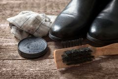 Polish cream,brush,dirty cloth and black boot. On wooden background stock photos